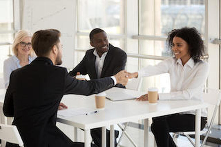Diverse businesspeople shaking hands during meeting in office